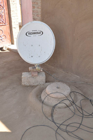 More traditional and newer technologies often sit side by side in the houses we have visited, as in the case of this satellite television dish and now seldom used wheat-grinding emplacement.
