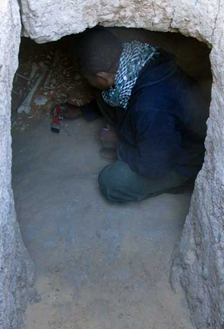 Mohamed crouching in the narrow western burial chamber of G244