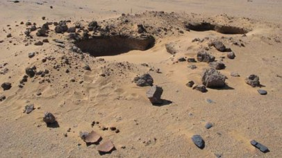 One of the looted chamber tombs with broken pottery on the surface.