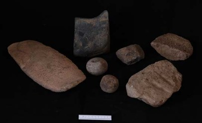 Assemblage of stone tools from D12.6.5: grindstone to left; spherical grinding stones in middle; enigmatic black stone object to rear