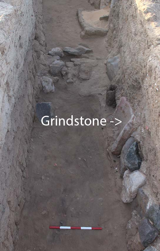 Grindstone built into revetment in alley E13.11