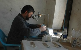 Conservation workroom with Maickel assessing a dish of Egyptian blue found in the cemetery, using a microscope for which the local blacksmith fabricated a stand (from a steel bedframe!).