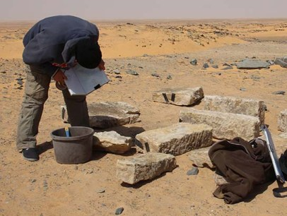 Michelle Gamble faces recording the stonework recovered from the shaft of pyramid tomb G320