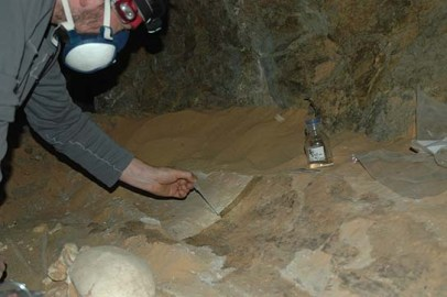 In a subterranean chamber beneath tomb G322, Maickel consolidating a section of coffin